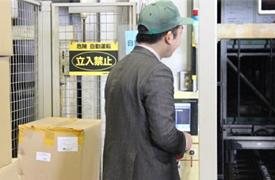 自動倉庫の状態を確認中の営業・安部